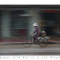 Woman With Hat On A Wet Bicycle by Jorgen Udvang in Jorgen Udvang